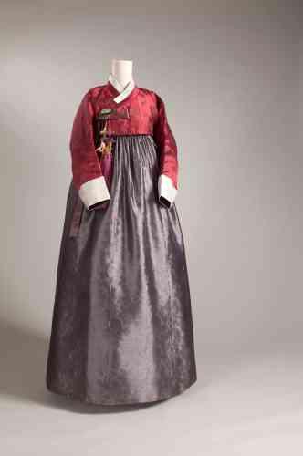 Le costume féminin par excellence : un mille-feuille de gazes tissées très fines pour la jupe à taille haute dissimulant les formes et un boléro court d'une couleur vive tranchante, retenu par un nœud (norigae), la décoration qui dit le rang.