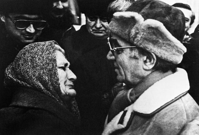 Le chanteur français d'origine arménienne, Charles Aznavour, discute avec une femme arménienne à son arrivée à Erevan, le 4 février 1989.