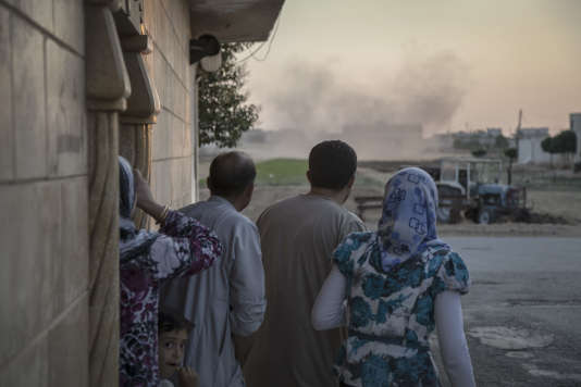 Des habitants de Tal Rifaat, une petite ville entre Alep et Azzaz, regardent un hélicoptère bombarder l'école, le 12 juillet.