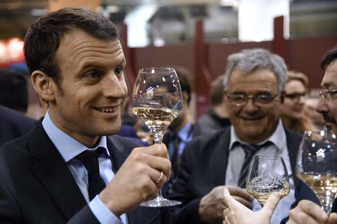 French Economy and Industry minister Emmanuel Macron tastes wine as he visits the Salon de l'Agriculture farm fair on March 3, 2016 in Paris. / AFP / DOMINIQUE FAGET