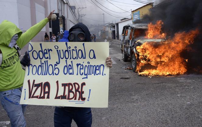Un étudiant vénézuélien manifestant contre le gouvernement de Nicolas Maduro, le 3mars, et portant une affiche disant : «Le pouvoir judiciaire est aux genoux du régime. Venezuela libre!»