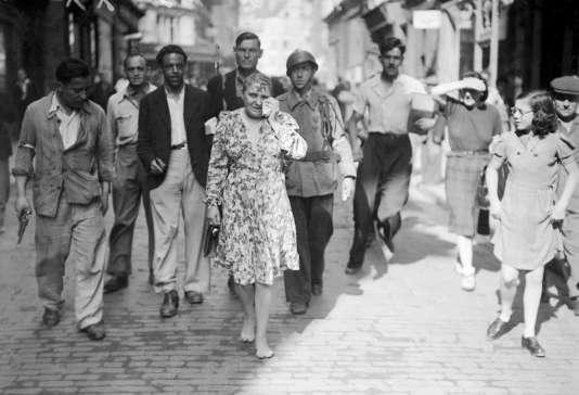 La photo, prise en août 1944, d'une femme accusée d'avoir collaboré avec les Allemands. Elle est obligée de défiler dans la rue, le crâne rasé, pieds nus, une croix gammée sur le front, après la Libération de Paris.
