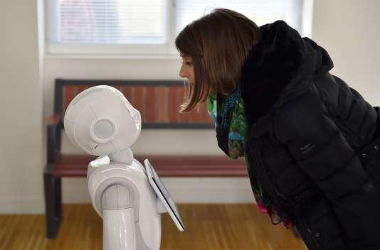 """Une femme interagit avec le robot """"Pepper"""", à la gare de Nort-sur-Erdre, le 2 mars 2016."""