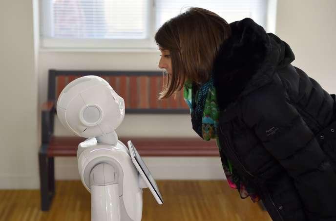 Une femme interagit avec le robot