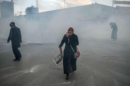 Une femme s'enfuit en courant tandis que la police antiémeute turque disperse les manifestants supportant le journal Zaman en les arrosant de gaz lacrymogène, le 4mars 2016 à Istanbul.