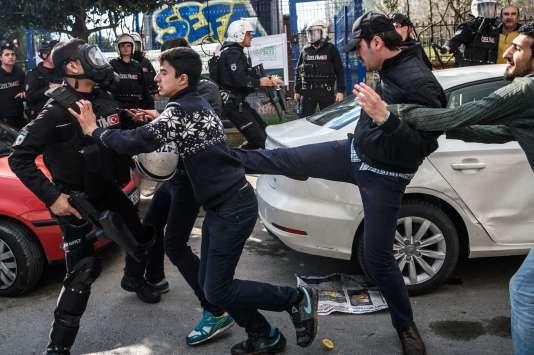 Un officier de police frappe un manifestant tandis que la police anti-émeute turque disperse les manifestants supportant le journal «Zaman», le 5 mars 2016 à Istanbul.