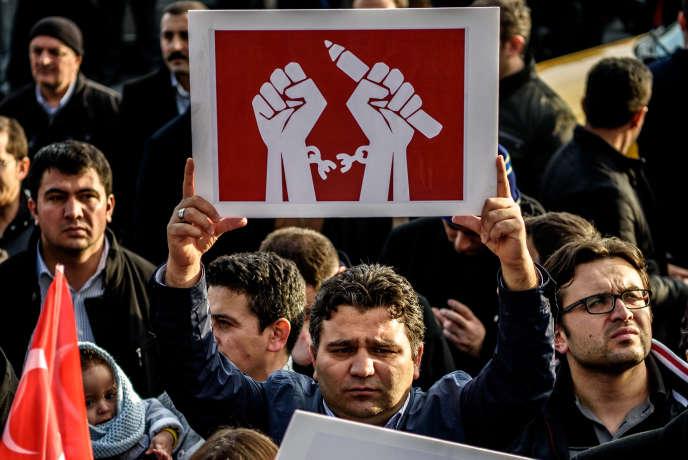 Un homme brandit une pancarte dénonçant les atteintes à la liberté de la presse en Turquie.  / AFP / OZAN KOSE