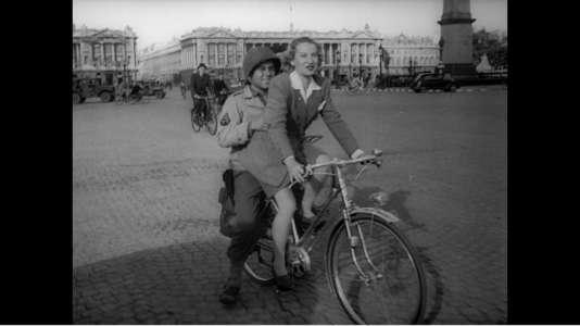 Une femme transporte un militaire sur le porte-bagages de sa bicyclette, place de la Concorde, dans un Paris libéré.