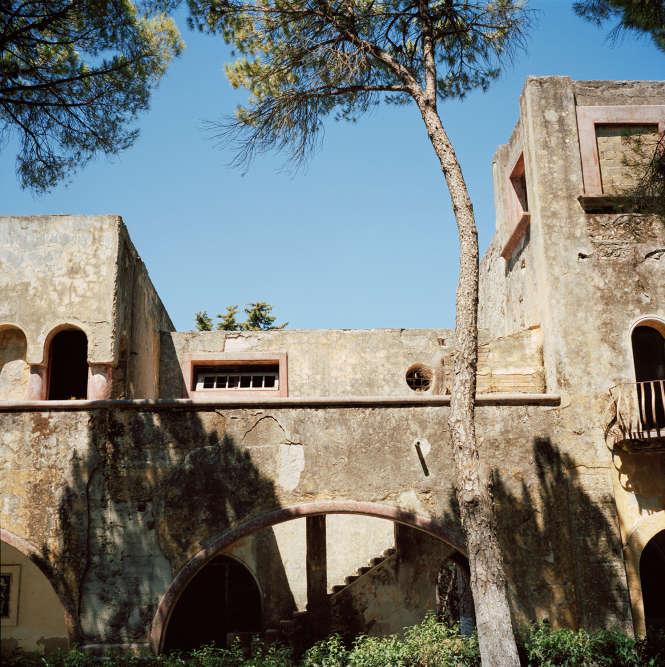 """Son bâtiment principal, construit en 1935 autour d'une grande place rectangulaire, accueillait une garnison, une école, un cinéma, des boutiques, un sanatorium et une Casa del fascio (""""Maison du fascisme"""")."""