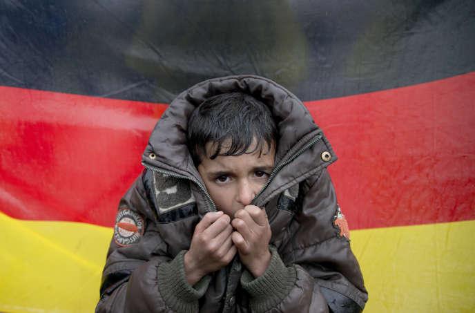 Un enfant migrant devant un drapeau allemand lors d'une manifestationdans le village grec d'Idomeni, le 9 mars 2016.
