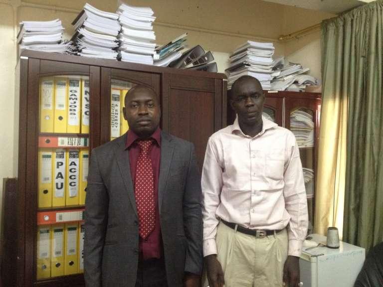 Lamin Bofang, coordonnateur de l'aide internationale ( à gauche) avec l'un de ses collaborateurs, dans son bureau au ministère des finances à Banjul.