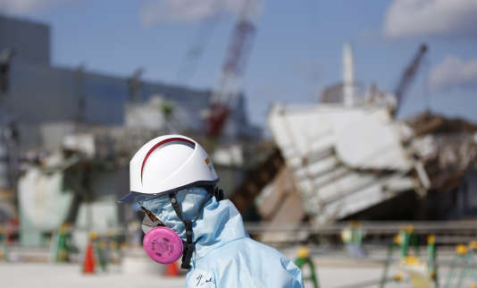 Un employé de Tepco marche devant le réacteur1 de la centrale nucléaire de Fukushima, au Japon, en février 2016.