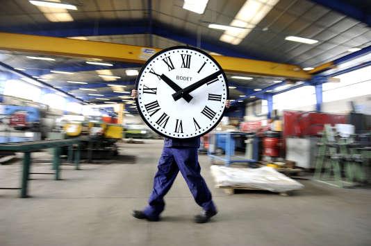 Un salarié de l'entreprise Bodet porte une horloge dans l'entreprise du Maine-et-Loire.