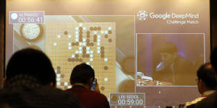 South Korean professional Go player Lee Sedol, right, is seen on the screen during the Google DeepMind Challenge Match against Google's artificial intelligence program, AlphaGo, at the media room in Seoul, South Korea, Wednesday, March 9, 2016. Computers eventually will defeat human players of Go, but the beauty of the ancient Chinese game of strategy that has fascinated people for thousands of years will remain, the Go world champion said Tuesday. (AP Photo/Lee Jin-man)