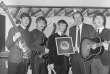 De gauche à droite, Paul McCartney, George Harrison, Ringo Starr, George Martin et John Lennon. A Londres, en1964, lors de la remise d'un disque d'argent.