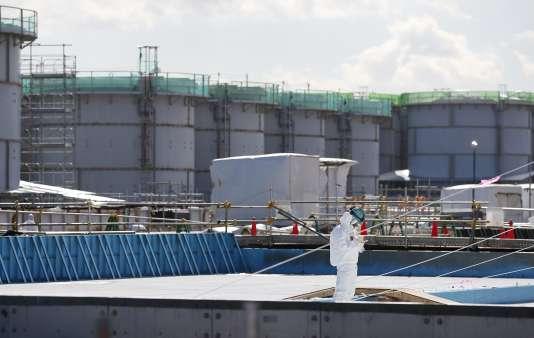 Un ouvrier du nucléaire devant des citernes qui stockent l'eau contaminée.