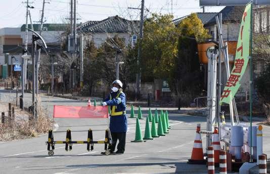 Un homme contrôle les entrées dans une zone résidentielle de Futaba (préfecture de Fukushima), le 12 février. Le lieu s'est en grande partie vidé de ses habitants à la suite de l'accident nucléaire du 11mars2011.