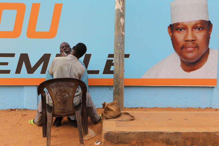 Un homme se fait raser devant une affiche de campagne de l'opposant emprisonné et candidat à la présidentielle, Hama Amadou à Niamey au Niger, le 15 février 2016.