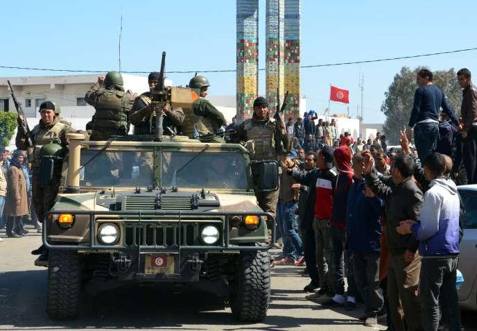 Des Tunisiens saluent un convoi militaire durant la visite du premier ministre à Ben Gardane, le 13 mars, une semaine après l'attaque.