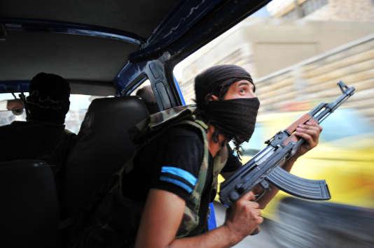 Des rebelles syriens guettent des snipers après l'attaque de la mairie dans le centre de Selehattin, près d'Alep, le 23 juillet 2012, au cours d'affrontements avec les troupes syriennes.
