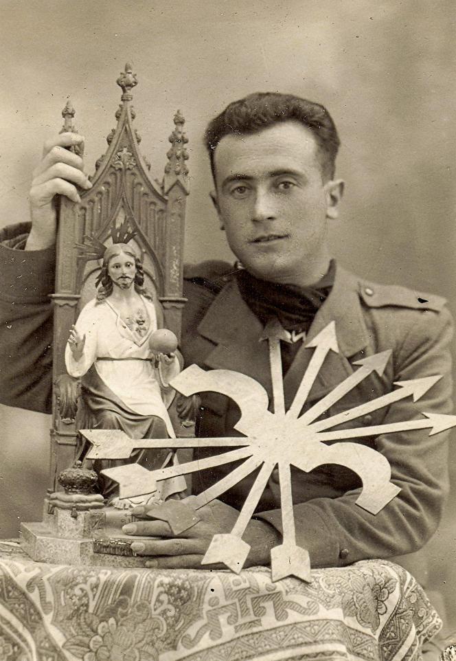 Un soldat nationaliste posant avec des symboles religieux et franquistes à Cadix, en 1937.