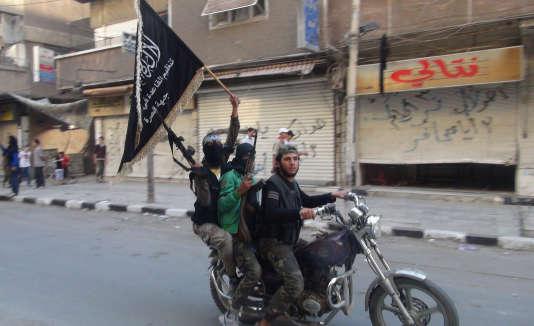 Des combattants du Front Al-Nosra, branche syrienne d'Al-Qaida, paradent dans le camp palestinien de Yarmouk, à la périphérie de Damas, le 28 juillet 2014.