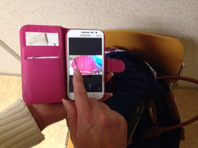 Rima fait défiler sur son téléphone portable les photos d'un pull qu'elle a tricoté.