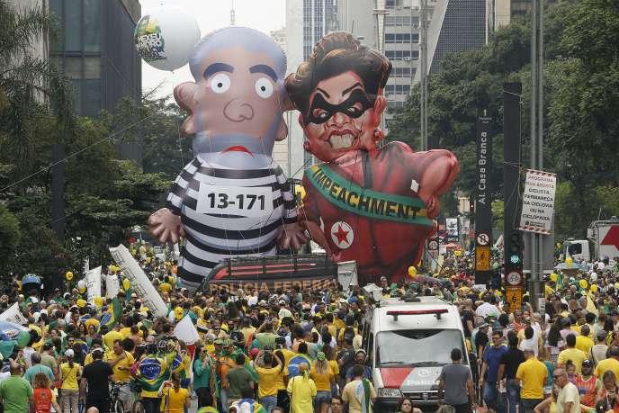 Ici à Sao Paulo, dimanche 13 mars, deux poupées gonflables géantes représentent l'ex-président Luiz Inacio Lula da Silva en prisonnier et l'actuelle présidente Dilma Roussef, en habits de voleuse.