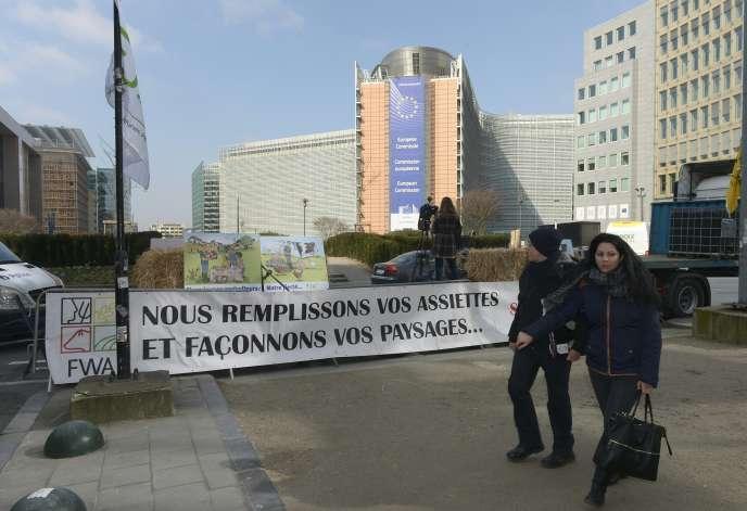Banderole « Nous remplissons vos assiettes et façonnons vos paysages», exposée près de la Commission de l'Union européenne pour protester contre la baisse des prix alimentaires à Bruxelles, le 14 mars.