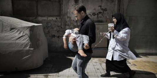 Un Syrien porte sa fille blessée hors d'un hôpital d'Alep, le 18 septembre 2012.
