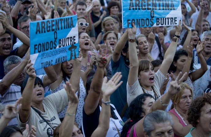 Des manifestants brandissent des pancartes contre le remboursement de la dette aux