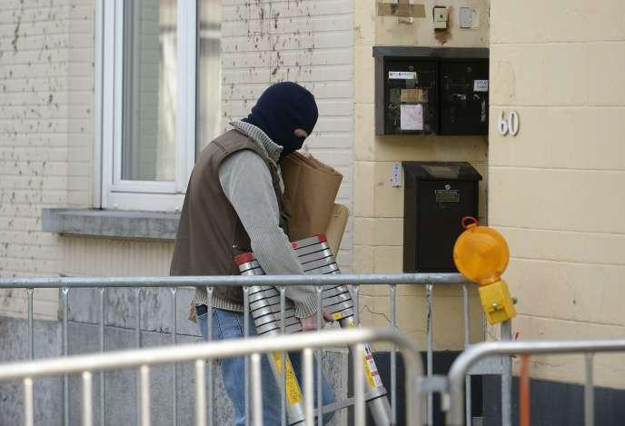 Un membre de la police belge sur les lieux de la fusillade qui a éclaté, mardi 15 mars, à Forest en Belgique au cours d'une perquisition de routine dans le cadre de l'enquête sur les attentats du 13 novembre.