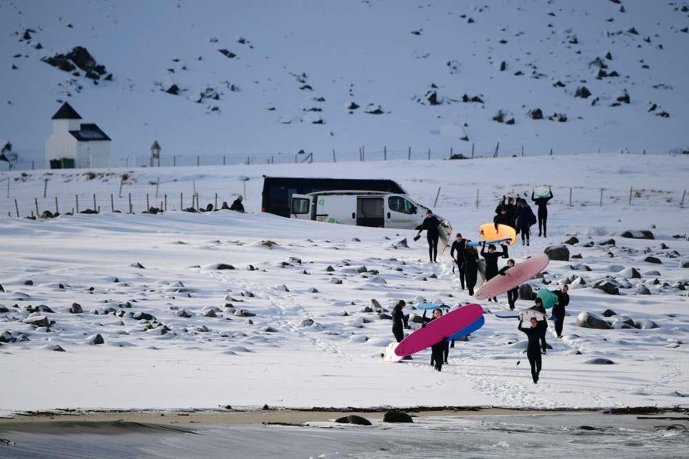 Un groupe de débutants arrive à son premier cours de surf hivernal.