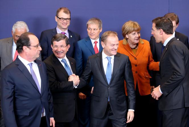 Le président du Conseil européen Donald Tusk serre la main du premier ministre turc Ahmet Davutoglu (au premier rang, deuxième à gauche) lors de la réunion des dirigeants de l'Union européenne avec la Turquie, le lundi 7 mars.