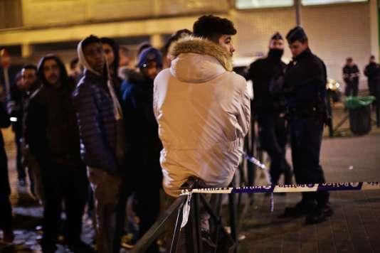 Place Oisiers, à Molenbeek, les habitants du quartier de la rue des Quatre-Vents attendent de rentrer chez eux, vendredi 18 mars.