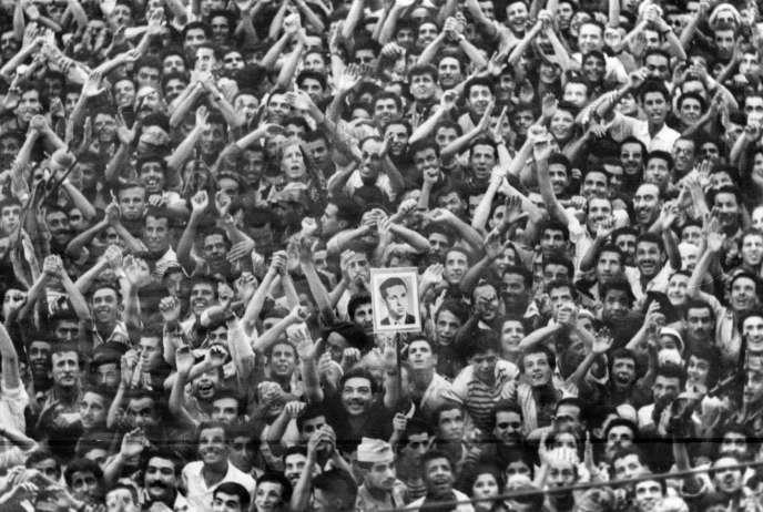 La foule acclame le secrétaire général du FLN Ahmed Ben Bella et brandit un  portrait de lui  pour l'accueillir à son arrivée à Alger le 4 août 1962. L'Algérie a proclamé son indépendance après la signature des accords d'Evian le 18 mars 1962.