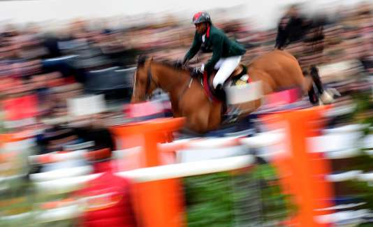 """Morocco's Abdelkebir Ouaddar riding Quickly De Kreisker competes in the """"Grand Prix Hermes"""" International Jumping Competition at the Grand Palais in Paris on March 20, 2016. / AFP / FRANCK FIFE"""