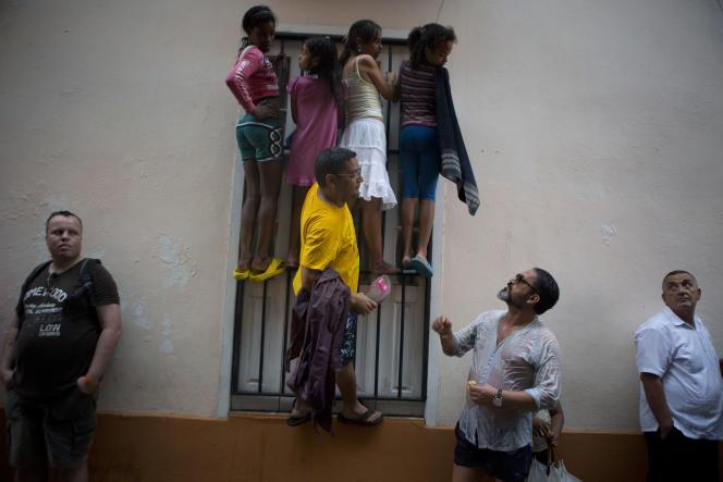 Des gens escaladent la barrière d'un balcon pour tenter d'apercevoir le président Barack Obama lors de sa visite de la cathédrale de la Havana Vieja, le 20mars.