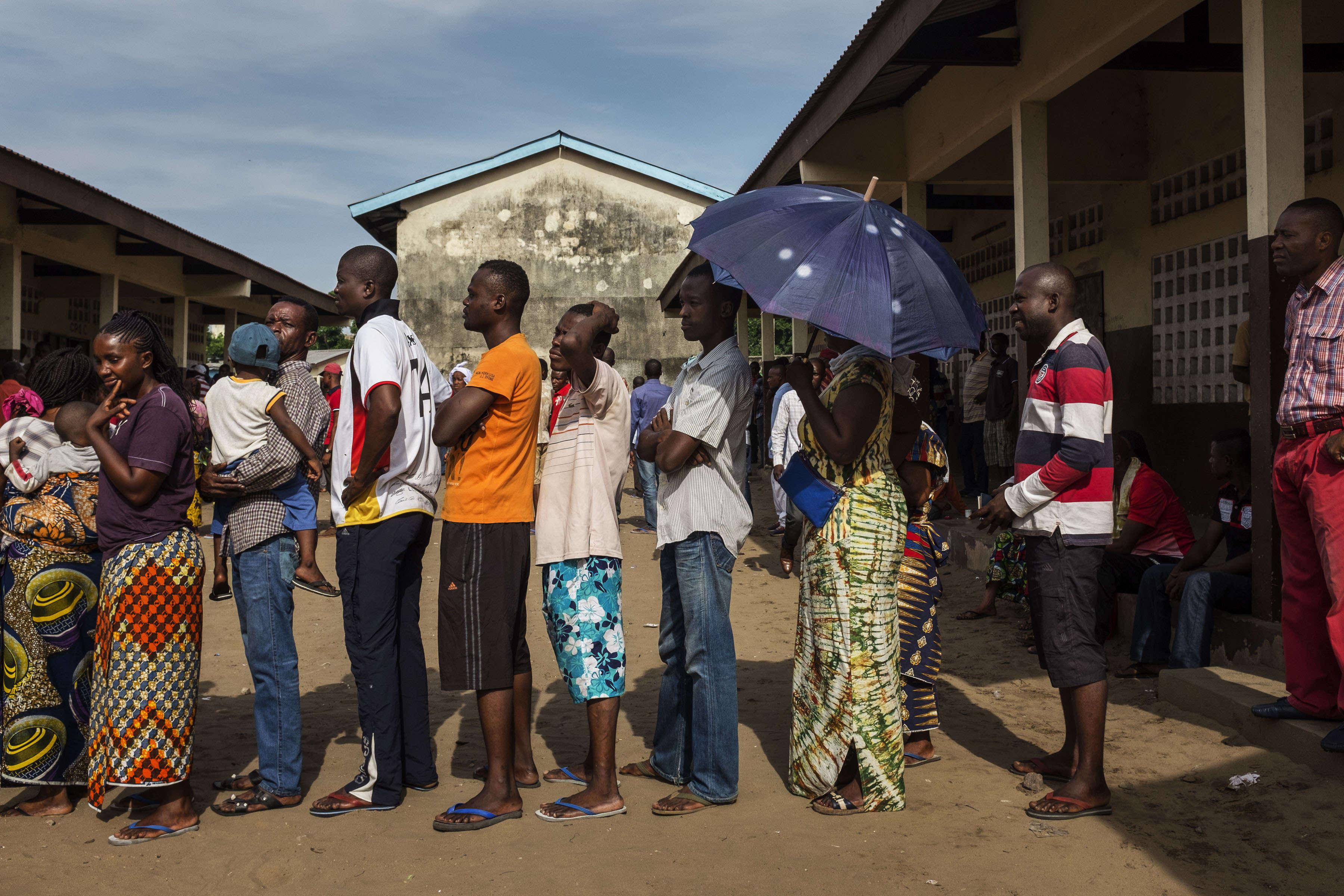 Des électeurs congolais font la queue à l'extérieur d'un bureau de vote dimanche 20 mars.