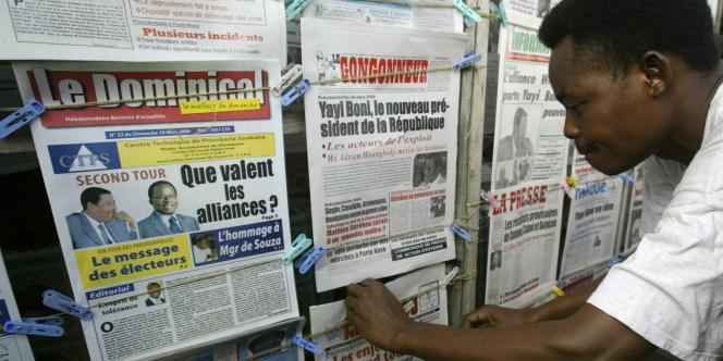 Un Béninois devant un kiosque à journaux.