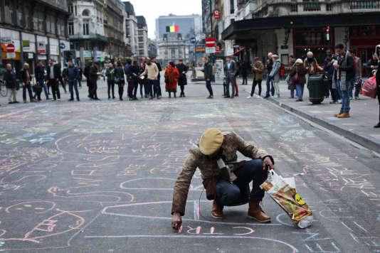 Place de la Bourse à Bruxelles, où les gens on commencé à se recueillir et écrire à la craie sur le sol, des messages de solidarité envers les victimes, mardi 22 mars.