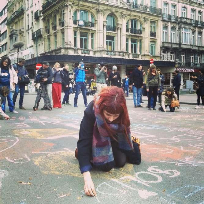 """Place de la bourse 400 personnes environ dessinent sur le sol avec des craies de toutes les couleurs. Messages de toutes sortes, beaucoup sont écrits en anglais, parce qu'""""on n'est plus ni flamands ni wallons aujourd'hui"""", dit un jeune type à vélo. I love Brux'hell. Let'us be happe. Love."""