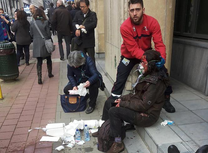 Cette photo d'un garde de sécurité privé venant en aide à une femme blessée devant la station de métro Maelbeek, à Bruxelles, le 22 mars, a été prise par un particulier.