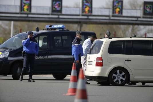 Des gendarmes français inspectent les véhicules au péage de Senlis, dans le nord de la France, le 22 mars.