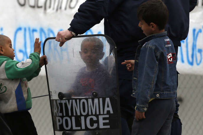 Des enfants migrants jouent avec le bouclier d'un policier, à Idomeni, en Grèce, le 23 mars 2016.