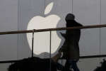 FILE - In this Dec. 23, 2013, file photo, a woman using a phone walks past Apple's logo near its retail outlet in Beijing. Even while it fiercely opposes the FBI's demand for help unlocking an encrypted iPhone used in the San Bernardino mass shootings, Apple has never argued that it isn't capable of doing what the government wants. While the FBI may have found an alternative solution in the San Bernardino case, experts say it's almost certain that Apple and other tech companies will keep increasing the security of their products, making it harder or perhaps even impossible for them to answer government demands for customers' data. (AP Photo/Ng Han Guan, File)