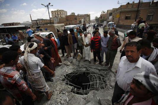 Des habitants de Sanaa, la capitale du Yémen, observent le lieu d'impact d'une bombe larguée lors d'un raid aérien par la coalition dirigée par l'Arabie saoudite, mercredi 23 mars.