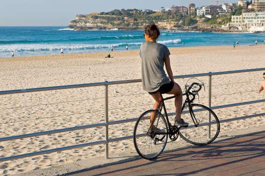 Une cycliste devant la célèbre plage de Bondi, à Sydney.