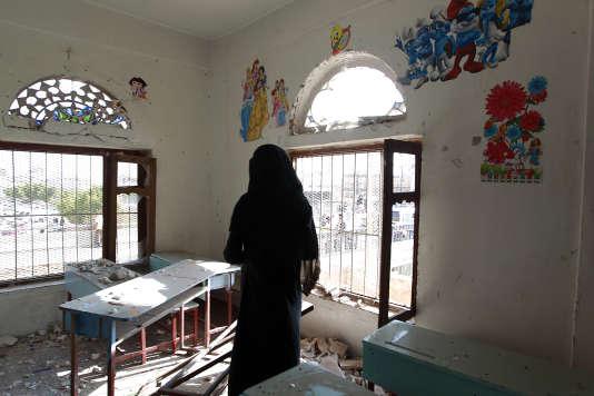 Une femme constate les dégâts dans une crèche de Sanaa après un bombardement de l'armée saoudienne, le 23 mars 2016.