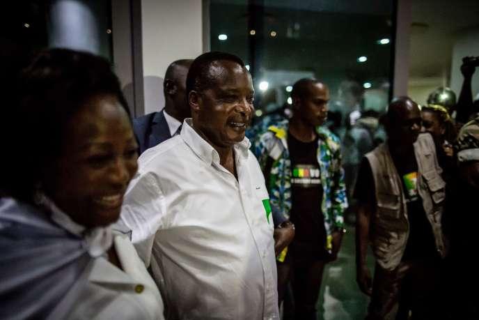 Le président sortant du Congo, Denis Sassou-Nguesso (en chemise blanche), accompagné de sa femme, Antoinette (à gauche), quitte son siège de campagne, quelques minutes après que la Commission électorale indépendante l'a déclaré vainqueur de l'élection présidentielle, jeudi 24 mars, à Brazzaville.